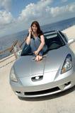 Seduta teenager sul cappuccio dell'automobile sul telefono delle cellule Fotografia Stock Libera da Diritti