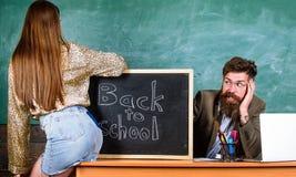 Sedutora do estudante Regras da disciplina do comportamento da escola Professor ou diretor de escola que olham absorbedly a menin imagens de stock