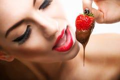 Seduzione - labbra femminili rosse che mangiano le fragole del cioccolato Immagini Stock Libere da Diritti