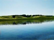 See auf einem ruhigen Ufer in einem glänzenden rasenden Himmel und in einer schönen Landschaft lizenzfreies stockbild