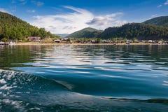 See Baikal nahe grünem Waldberg und -Holzhaus stockfotografie