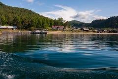 See Baikal nahe grünem Waldberg und -Holzhaus lizenzfreies stockbild