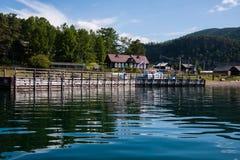 See Baikal nahe grünem Waldberg und -Holzhaus lizenzfreie stockfotografie