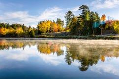See bedeckt mit Morgen-Nebel am Sonnenaufgang und an der Reflexion im Wasser Stockbilder