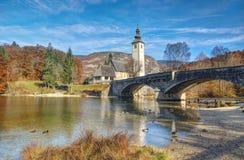 See Bohinj und Kirche Johannes der Baptist, Slowenien - Herbstansicht Stockbild
