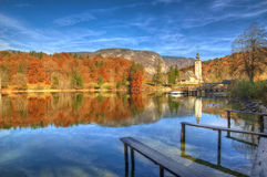 See Bohinj und Kirche Johannes der Baptist, Slowenien - Herbstansicht Lizenzfreie Stockfotos
