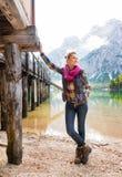 See Bries-Frau, die am hölzernen Pier, an der Entspannung und am Lächeln stillsteht Lizenzfreie Stockbilder