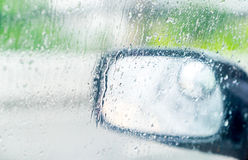 See through car window to side rear-view mirror in raining day.  Royalty Free Stock Photography