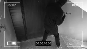 See CCTV as a burglar breaking in through the door with a crowbar.  Stock Photo