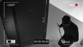 See CCTV as a burglar breaking in through the door with a crowbar stock image
