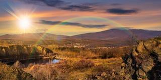 See in den Bergen bauen nahe Stadt bei Sonnenuntergang ab Lizenzfreie Stockfotografie