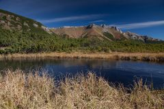 See in den Bergen mit felsigen Spitzen auf dem Hintergrund lizenzfreie stockfotografie