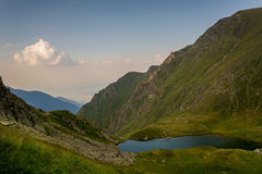 See in den Bergen und in einer kleinen Wolke Stockfoto