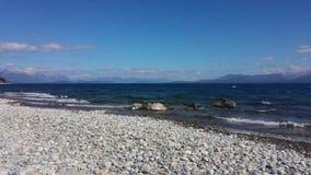 See des Argentiniens Süd Strand von weißen Steinen Haarscharfes Wasser und Berge im Hintergrund stock footage