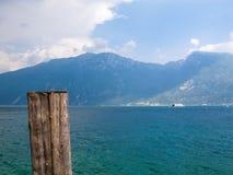 See Garda mit einem hölzernen Pfosten im Vordergrund und einer Fähre im Hintergrund Lizenzfreie Stockfotos