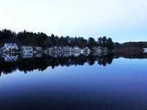 See-Häuser auf einem ruhigen blauen See Lizenzfreies Stockbild