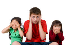 See hear speak no evil. Two young girls and a teenage boy act out the proverb. see hear speak no evil Royalty Free Stock Image