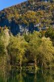 See im Herbst mit kleinem Haus und großen Bergen mit Bäumen lizenzfreie stockbilder