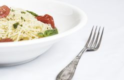 Plate of spaghetti with cherry tomatoes, basil and grated cheese stock images