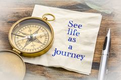 See life as a journey - text on napkin. See life as a journey  - inspiraitonal handwriting on a napkin with an antique brass compass Royalty Free Stock Image