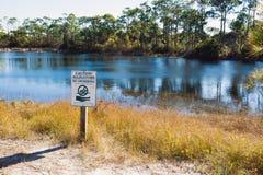 See mit Alligatoren in Florida. Schild, das Schwimmen verbietet Stockbilder