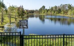 See mit Alligatoren in Florida Wegweiser, der Schwimmen verbietet Lizenzfreie Stockfotografie