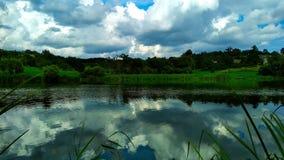 See mit Bäumen im Hintergrund und in einer Reflexion des Himmels im Wasser lizenzfreie stockfotos