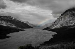 See mit einem kleinen Boot und einem Regenbogen Stockfotografie