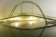See mit einer Brücke auf einer nebeligen Nacht Lizenzfreie Stockbilder