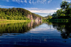See mit Hügeln und roter Klippe Lizenzfreies Stockbild