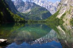 See mit haarscharfen Bergen des Wassers im Frühjahr Ein kleiner See in der Alpenansicht von einem Ufer Reflexion von Bergen herei stockbild