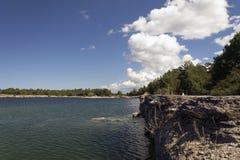 See mit Stein und einer Klippe Lizenzfreies Stockfoto