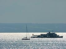 See mit Tausenden der funkelnden Stellen und der Berge im Hintergrund mit einem Schiff und einem Segelboot stockbild