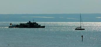See mit Tausenden der funkelnden Stellen und der Berge im Hintergrund mit einem Schiff und einem Segelboot 2 lizenzfreies stockbild