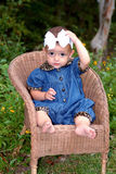 See My Bow. A cute little girl with a big bow in her hair sitting in a child's wicker chair wearing a denim outfit trimmed in leopard print Royalty Free Stock Images