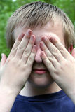 See No Evil. Preteen boy with hands covering his eyes royalty free stock images