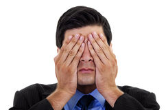See no Evil. Stock image of businessman covering his eyes with his hands, over white background royalty free stock photos