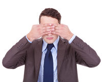 See no evil. Business man making the see no evil gesture over white . young businessman covering his eyes with his hand Stock Images