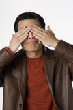 See no evil. Young Filipino man covers his eyes Royalty Free Stock Images