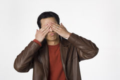 See no evil. Young Filipino man covers his eyes Royalty Free Stock Photo
