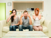 See no evil, hear no evil, speak no evil. Portrait of three friends sitting on couch imitating see no evil, hear no evil, speak no evil conept Royalty Free Stock Photos