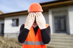 See no evil sign made by male builder. In front of renovated house Stock Image