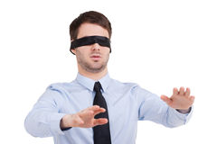 See no opportunity. Young businessman in blindfold stretching out hands while standing isolated on white Stock Photos