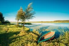 See oder Fluss und altes hölzernes blaues Rudersport-Fischerboot an schönem Stockbild