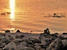 See Okeechobee-Sonnenuntergang und Felsen-Steinhaufen stockfoto