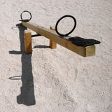 See-saw. Empty wooden teeter-totter or seesaw with shadow - negative birthrate concept royalty free stock photos