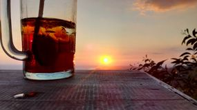 See the sunset over the hill and a glass of tea stock images