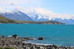 See Tekapo zu den Bergen mit Schnee auf Spitzen NZ Stockfotos
