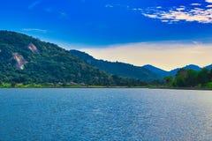 See in Thailand mit blauem Himmel und Bergen im Hintergrund stockfotografie