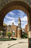 See trough of Hospital Sant Pau Barcelona Spain Europe. View through one of the gates of the gardens of Hospital Sant Pau Barcelona Spain with bleu cloudy skie Royalty Free Stock Photo